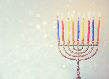 Low key image of jewish holiday Hanukkah background with menorah Burning candles over aqua glitter background