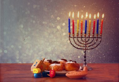 Jewish holiday Hanukkah with menorah, doughnuts and wooden dreidels (spinning top).