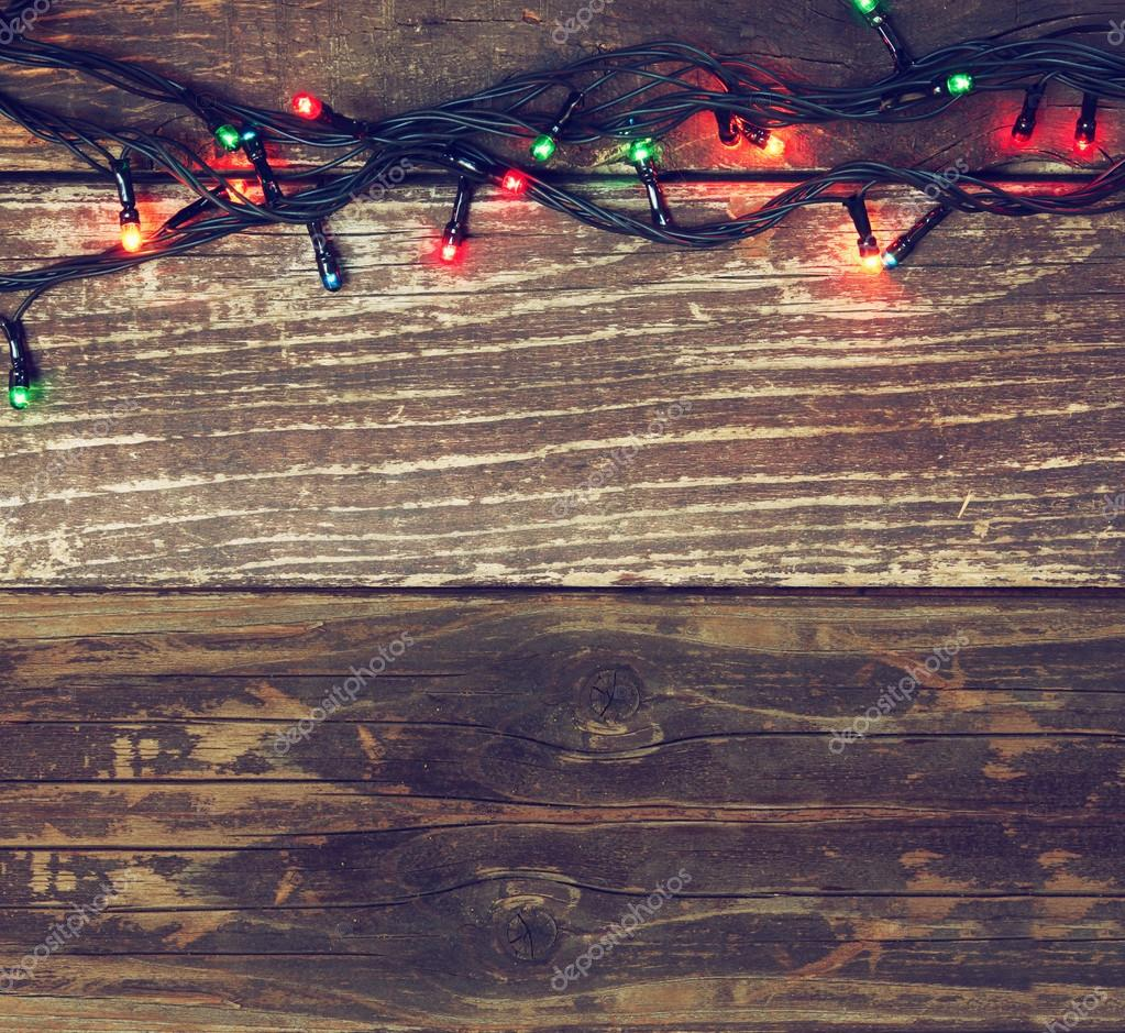 Colorful Christmas lights on wooden rustic background. filtered ...