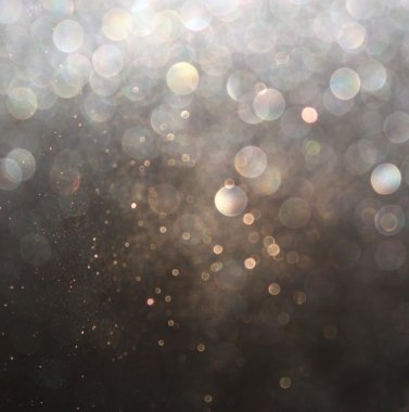 Glitter vintage lights background. silver and black. defocused.