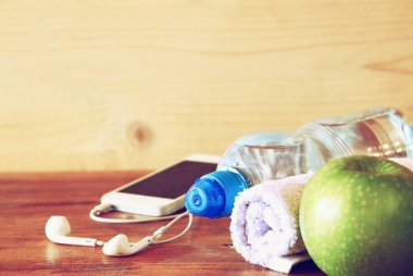 Low key  image of fitness concept with bottle of water, mobile phone with earphones, towel and apple over wooden background. filtered image with selective focus