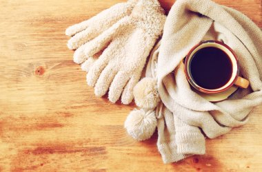 Cup of black coffee with  a warm scarf  on wooden background. filreted image