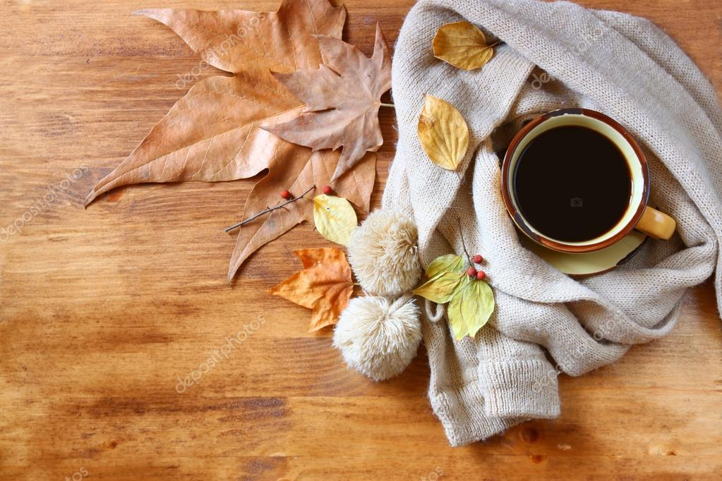 Top view of Cup of black coffee with autumn leaves, a warm scarf on wooden background. filreted image