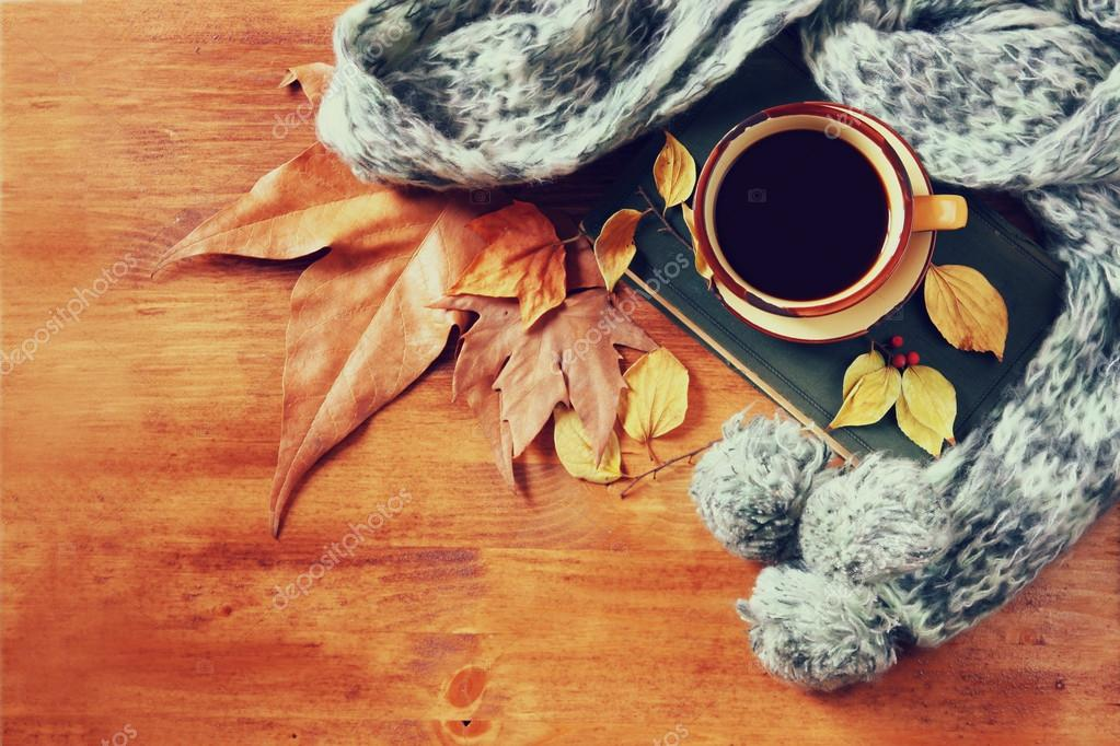 Top view of Cup of black coffee with autumn leaves, a warm scarf and old book on wooden background. filreted image