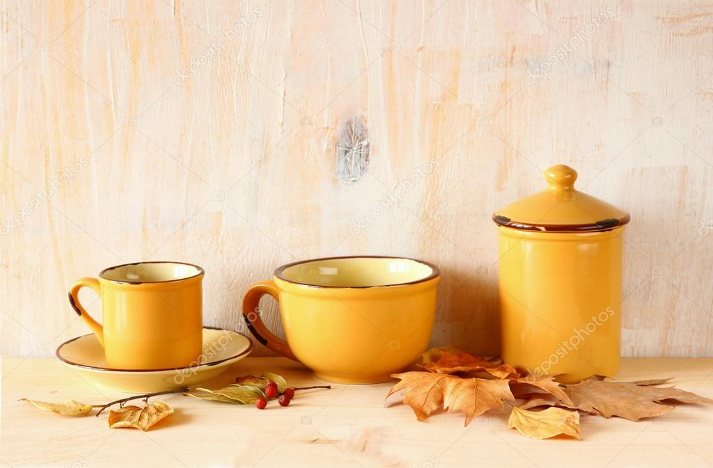 b6e73b4a730 Set of coffee mugs and old jar over wooden rustic table and autumn leaves.  filtered