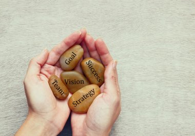 Woman holding river stones with words written on them. strategy and success concept