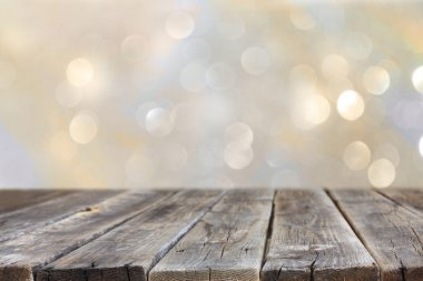 Rustic wood table in front of glitter silver and gold bright bokeh lights