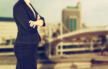 Woman in business suit on a city building background. filtered image
