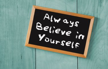 Top view of blackboard with the phrase always believe in yourself, over wooden background
