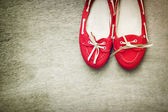 Fotografia Vista superiore di scarpe donna rossa indossato sopra legno fondo strutturato. filtro stile Instagram