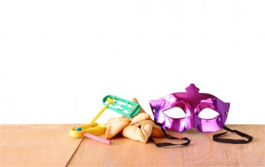 Hamantaschen cookies or hamans ears, noisemaker and mask for Purim celebration (jewish holiday) with isolated background