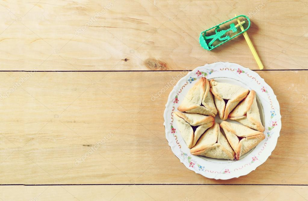 Top view of Hamantaschen cookies or hamans ears and noisemaker for Purim celebration (jewish holiday)