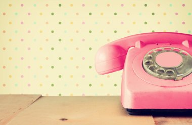 Retro pastel pink telephone on wooden table and abstract retro geometric pastel pattern Background. retro filtered image