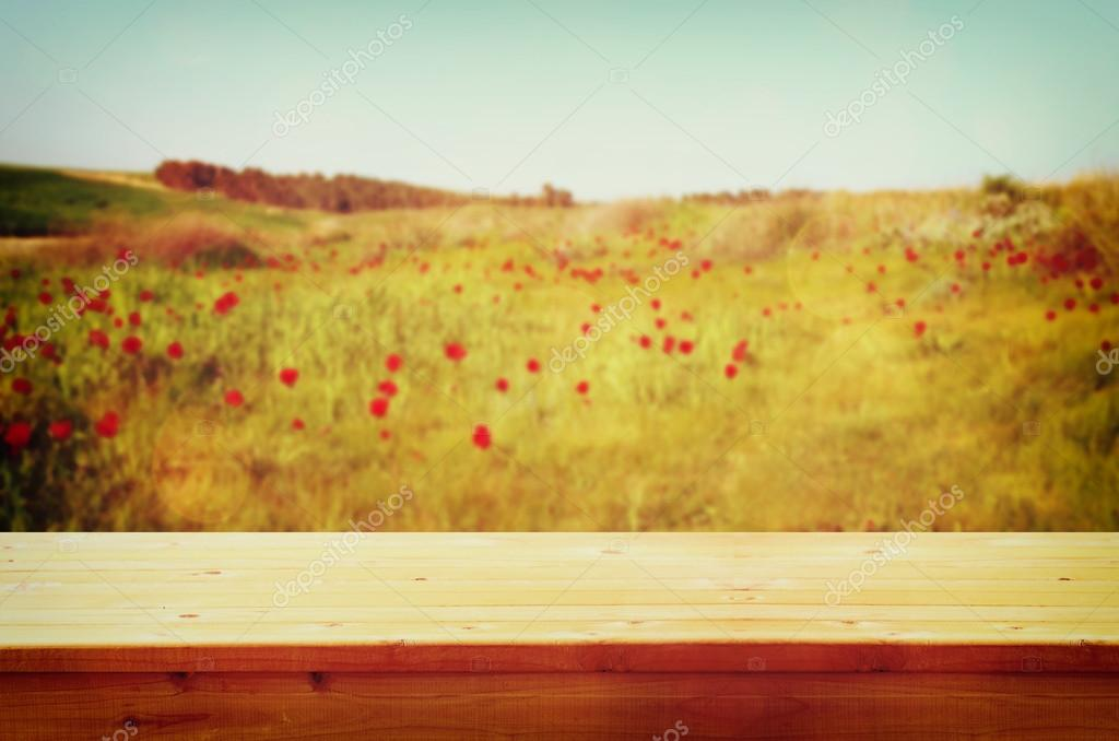 Wood board table in front of summer landscape of field with many flowers . background is blurred
