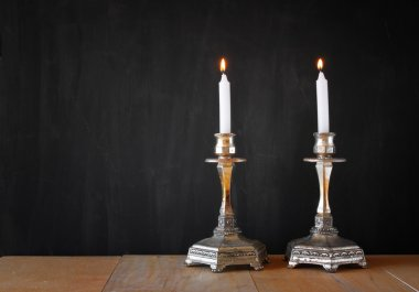 Two candlesticks with burning candels over wooden table and blackboard background