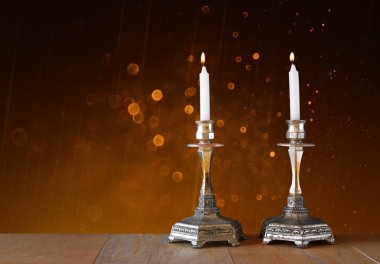 Two candlesticks with burning candles over wooden table and vintage glitter background