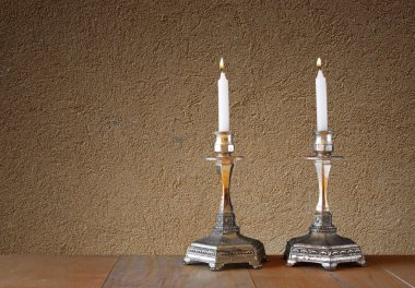 Two candlesticks with burning candles over wooden table and textured wall background