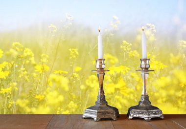 Two candlesticks with burning candles over wooden table and flower background