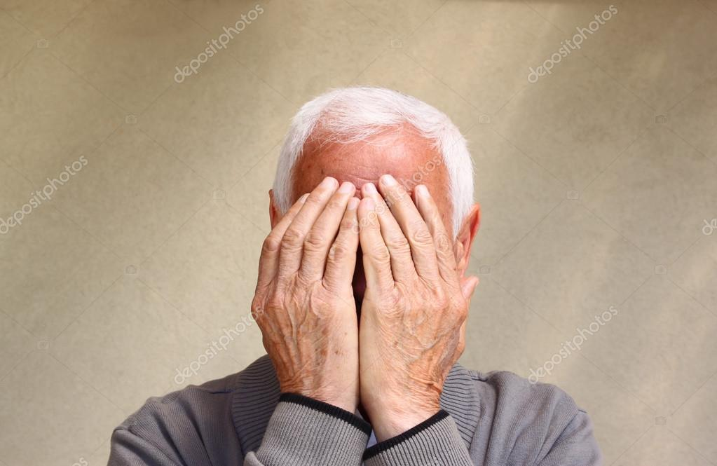Portrait of senior man covering his face with his hands