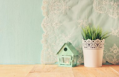 Vintage Flower pot and lantern as a bird house against mint wall and antique lace fabric