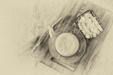 Image of greek cheese and bulgarian cheese on wooden table over wooden textured background. Symbols of jewish holiday - Shavuot. Black and white style photo.