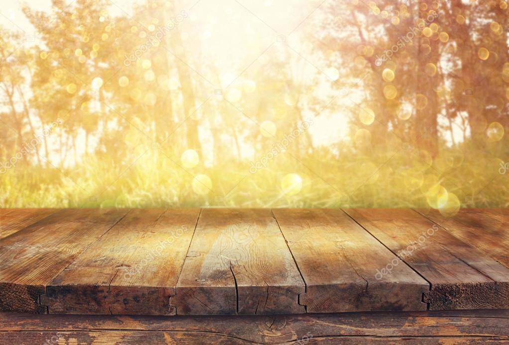 Vintage wooden board table in front of dreamy forest landscape with lens flare.