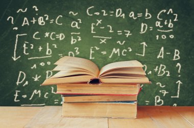 Image of school books on wooden desk over green background with formulas. education concept