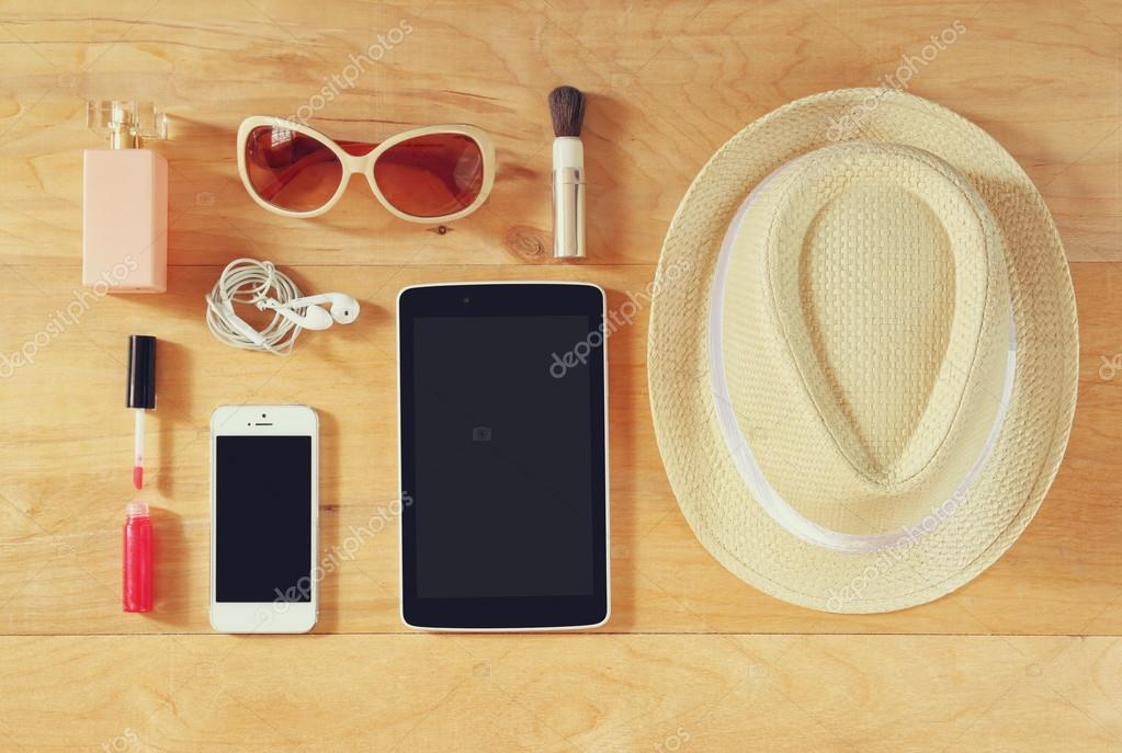 Top view image of woman accessories , different objects on wooden background.