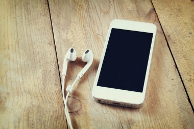 Top view of white smart phone and earphones on wooden table