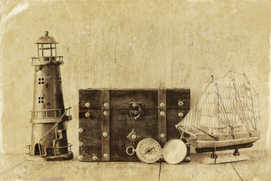 Antique compass, vintage lighthouse, wooden boat and old chest on wooden table. black and white style old photo