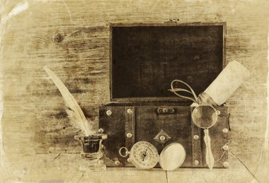 Antique compass, inlwell and old wooden chest on wooden table.  black and white style old photo