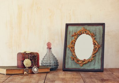 Image of victorian vintage antique classical frame, jewelry and perfume bottles on wooden table. filtered image