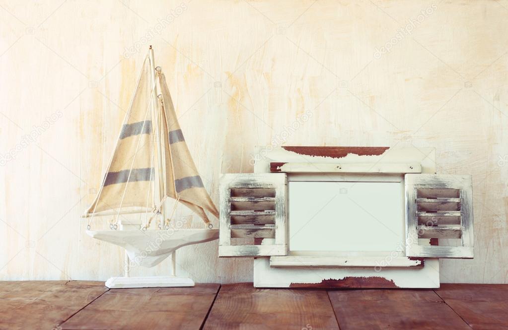 Marco antiguo de madera vintage blanco y barco de vela en la mesa de ...