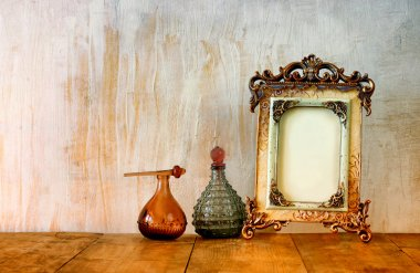 image of victorian vintage antique classical frame and perfume bottles on wooden table. filtered image