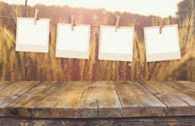 Old polaroid photo frames hanging on a rope with vintage wooden board table in front of wheat field landscape