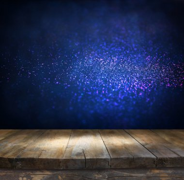 rustic wood table in front of glitter silver, blue, and gold bright bokeh lights