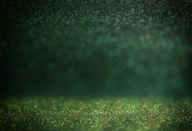glitter vintage lights background. gold, silver, green and black. de-focused.