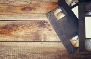 stack of VHS video tape cassette over wooden background. top view photo. retro style image