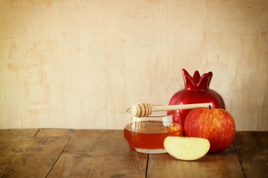 rosh hashanah (jewesh holiday) concept - honey, apple and pomegranate over wooden table. traditional holiday symbols.