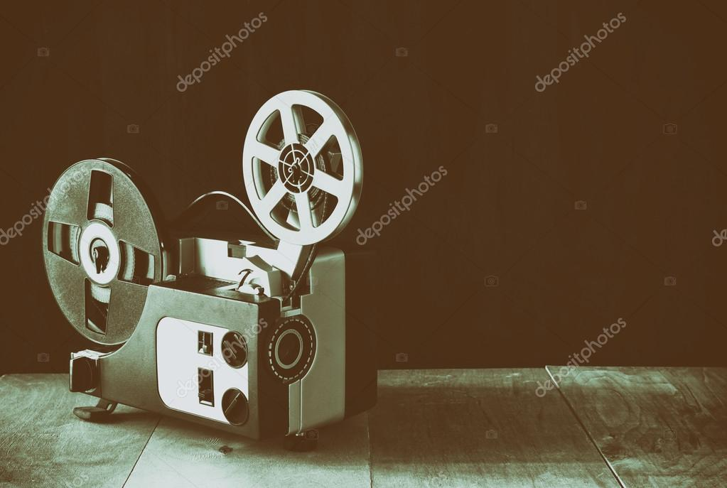 Old 8mm Film Projector over wooden table and textured