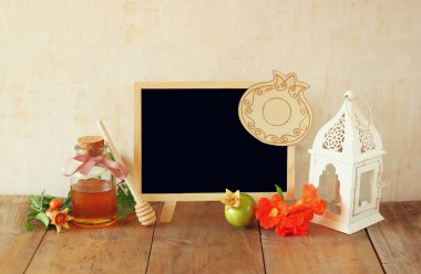 rosh hashanah (jewesh holiday) concept - blackboard, honey, apple and pomegranate over wooden table. traditional holiday symbols.