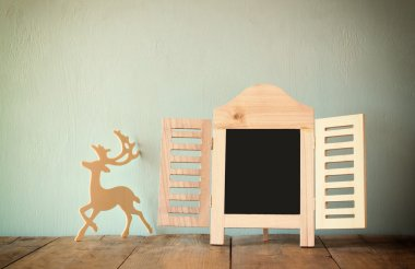 abstract filtered photo of decorative chalkboard frame and wooden deer over wooden table. ready for text or mockup