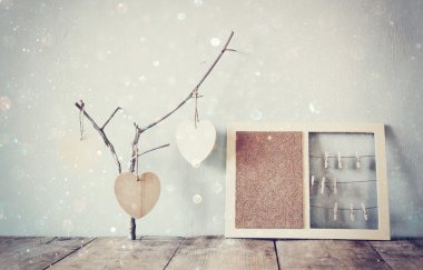 decorative bulletin board with rops and wooden clothespins and hanging hearts over wooden table. ready for text or mockup. retro filtered image