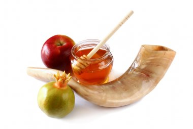 rosh hashanah (jewesh holiday) concept - shofar (horn), honey, apple and pomegranate isolated on white. traditional holiday symbols.