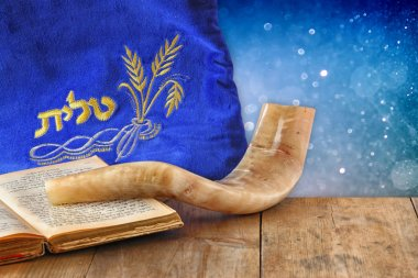 image of shofar (horn) and prayer case with word talit (prayer) writen on it. room for text. rosh hashanah (jewish holiday) concept . traditional holiday symbol.