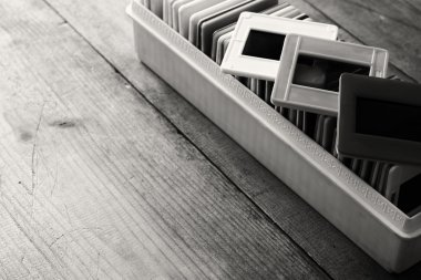 black and white close up image of old slides frames and old camera over wooden table