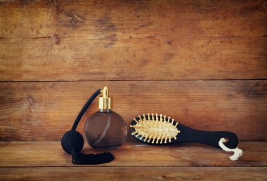 photo of vintage perfume bottle next to old wooden hairbrush on wooden table. retro filtered image