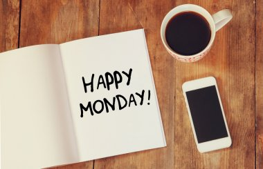 notebook with the phrase happy monday written on it, coffee cup and smart phone. filtered image
