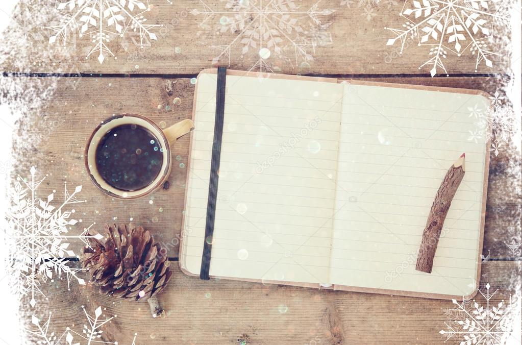 top image of open notebook with blank pages, next to pine cones and cup of coffee over wooden table. top image, glitter overly with snowflakes.