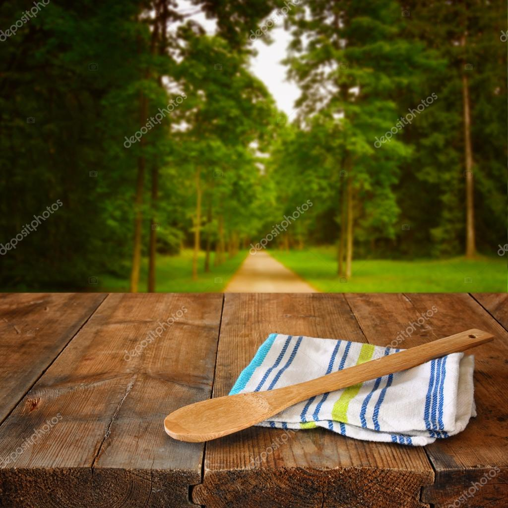 Kitchen utensils on tablecloth on wooden textures table against autumnal forest background.